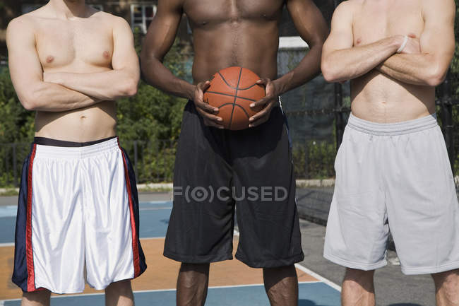 Low section of three basketball players in row — Stock Photo
