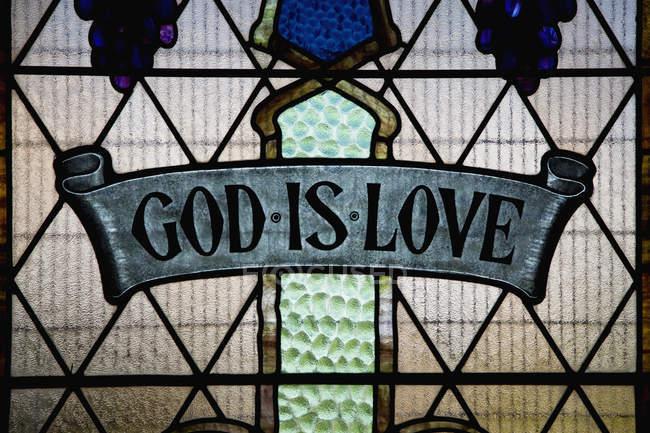 Gott ist Liebe-Schriftzug in Glasmalerei-Fenster — Stockfoto