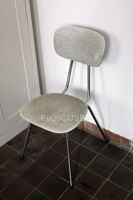 Cadeira vintage no chão cultivada no canto — Fotografia de Stock