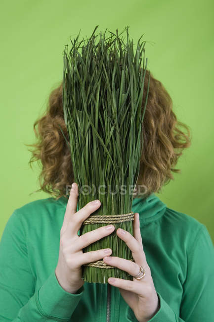 Woman holding a tied bunch of cut grass in front of face — Stock Photo