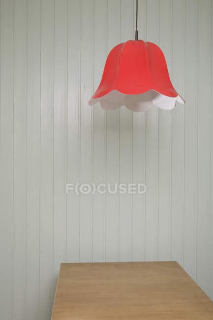 Lamp shade hanging above wooden table — Stock Photo