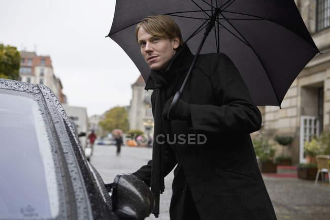Homme tenant un parapluie et ouvrant une porte de voiture — Photo de stock