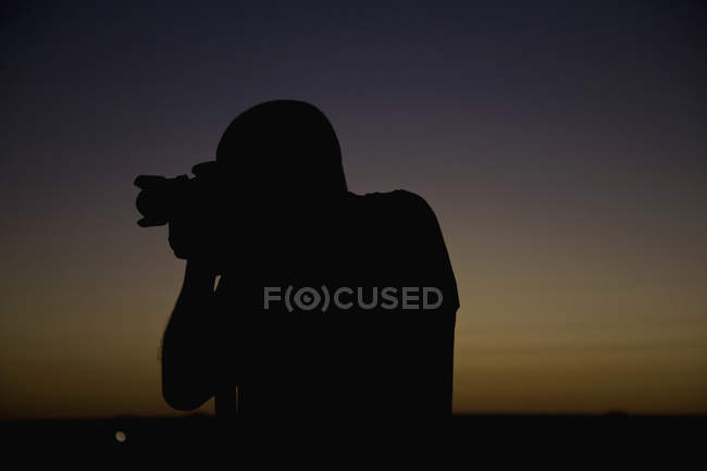 Silhouette du photographe en contre le coucher de soleil crépuscule dky — Photo de stock
