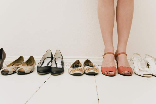 Bassa sezione di donna che indossa scarpe e in piedi in fila di scarpe da donna — Foto stock