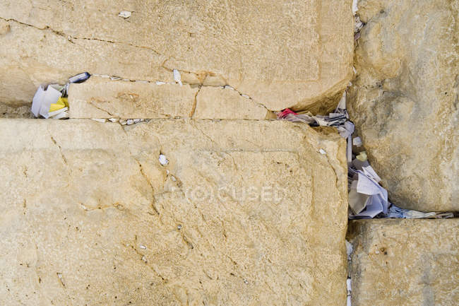 Slips of paper with prayers in crevices of wall — Stock Photo
