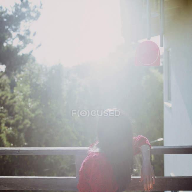 Frau sitzt auf Balkon im hellen Sonnenlicht — Stockfoto