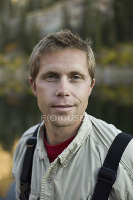 Портрет усміхнений чоловік зі світлим волоссям і блакитні очі, стоячи в природі — стокове фото