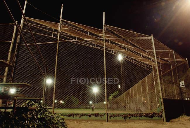 Arame farpado no campo de esporte iluminado à noite — Fotografia de Stock
