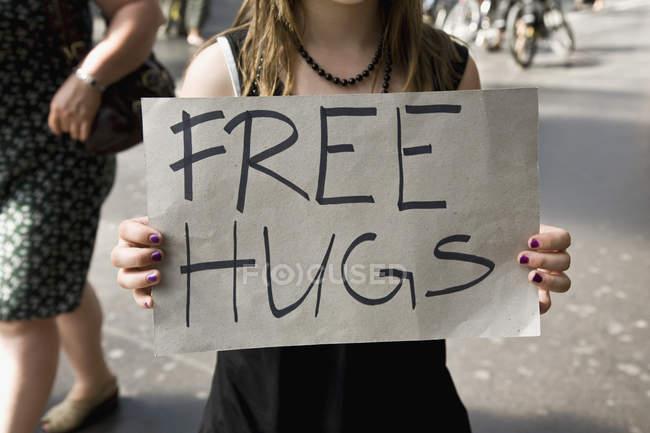 Молода жінка, проведення табличка безкоштовні обійми — стокове фото