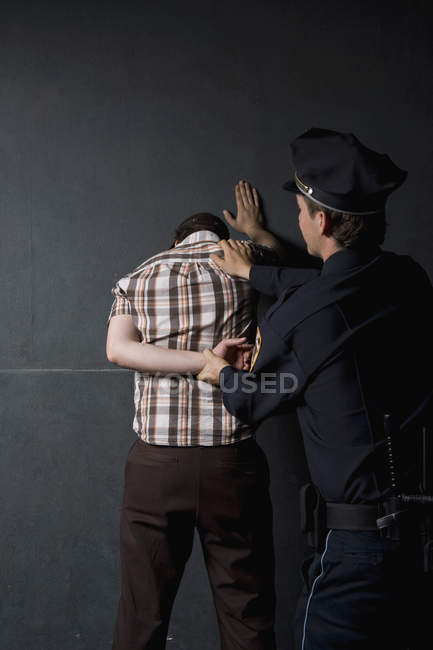 Police officer arresting criminal in front of black wall — Stock Photo