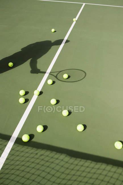 Sombra del jugador de tenis en cancha con pelota de tenis - foto de stock