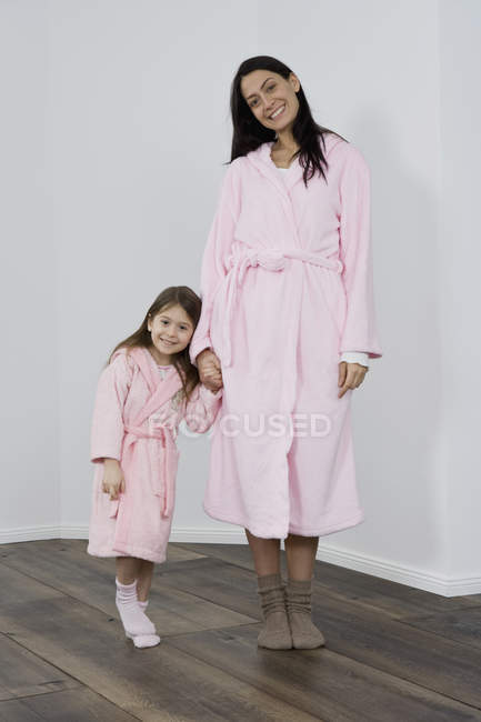 Una madre y una hija con rosa albornoz cogidos de la mano - foto de stock