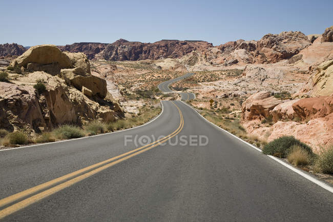 Winding road amid arid landscape on sunny day — Stock Photo