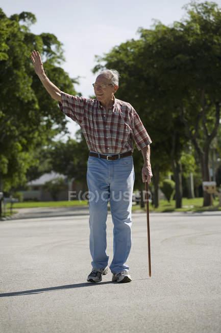 Un uomo anziano che cammina per strada e saluta — Foto stock