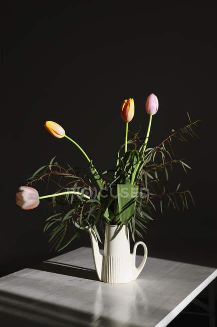 Stillleben mit Strauß Tulpen in Gießen kann auf Tisch — Stockfoto