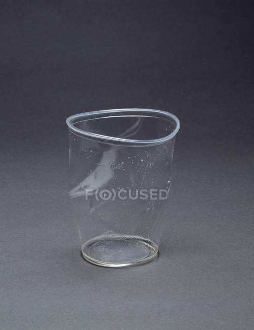 Empty crushed plastic cup on grey backdrop — Stock Photo