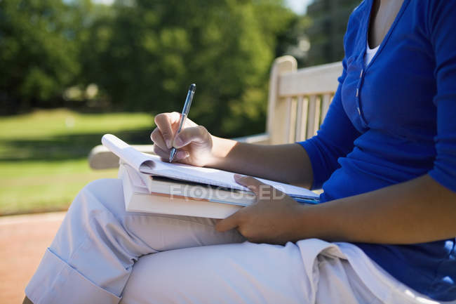 Midsection of  young woman writing at terrace — Stock Photo