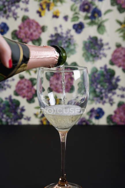 Обтинання жіночих рук розливу келих шампанського — стокове фото