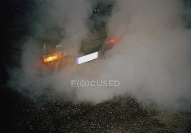 Rückansicht eines Autos, das nachts Abgase ausstößt — Stockfoto