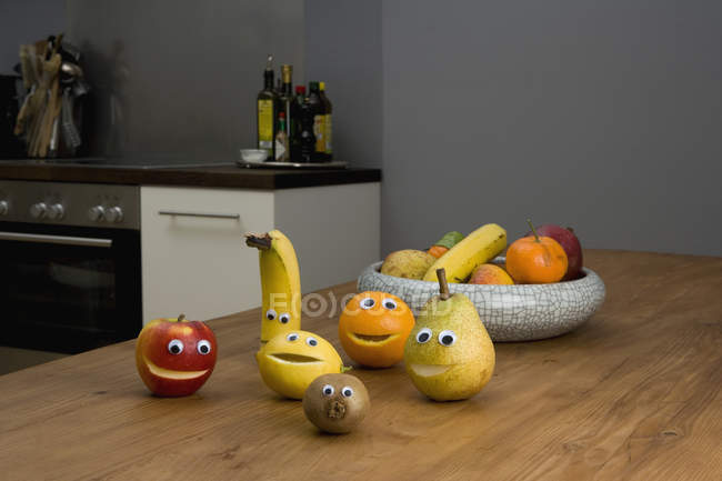 Fruit with smiley faces on  kitchen table — Stock Photo