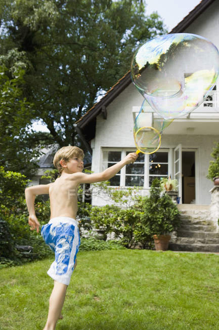 Boy making a bubble with a bubble wand in garden — Stock Photo