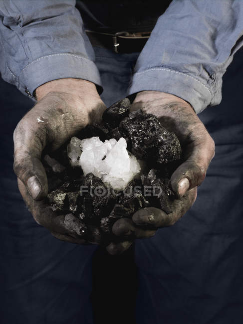 Crop miner holding quartz crystals in cupped hands — Stock Photo