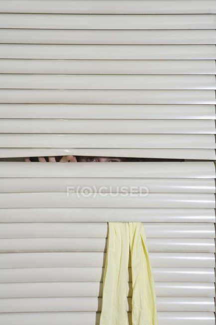 Человек, подглядывающий через оконные жалюзи — стоковое фото