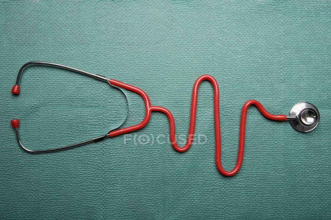 Stethoscope in shape of a normal EKG graph on green background — Stock Photo