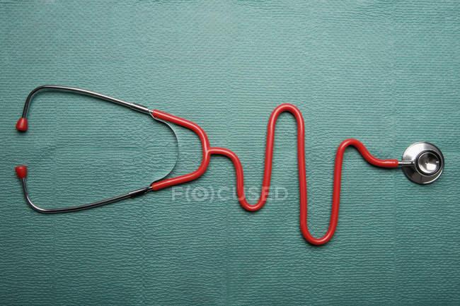Estetoscópio em forma de um gráfico EKG normal sobre fundo verde — Fotografia de Stock