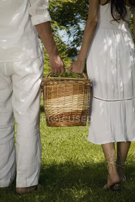 Niedrigen Bereich junges Paar mit Picknick-Korb zusammen auf Rasen — Stockfoto