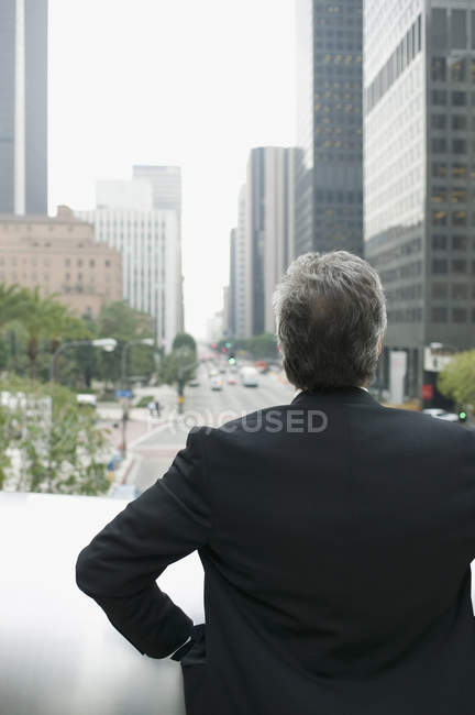 Businessman standing on a balcony in the financial district — Stock Photo
