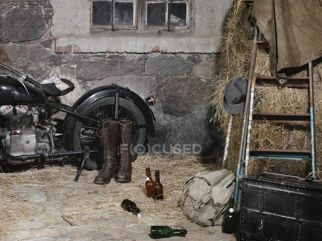 Natureza morta da motocicleta vintage com botas de equitação e garrafas de cerveja no feno — Fotografia de Stock