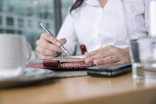 Обтинання жінка, сидячи за столом і використання особистих Організатор — стокове фото