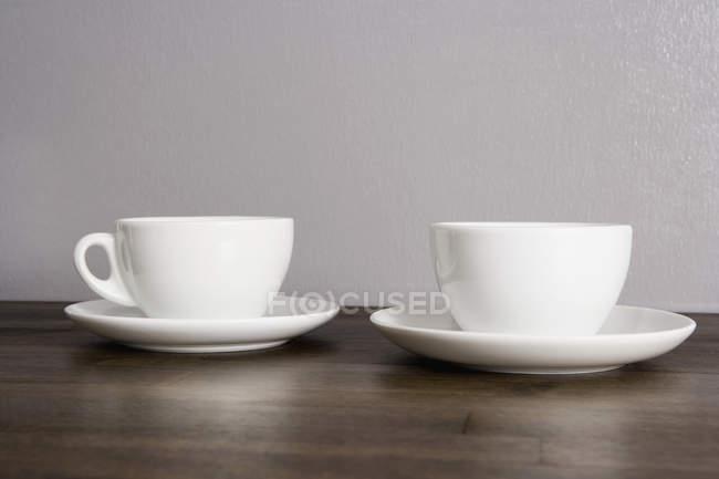 Zwei weiße Keramiktassen auf dem Tisch — Stockfoto