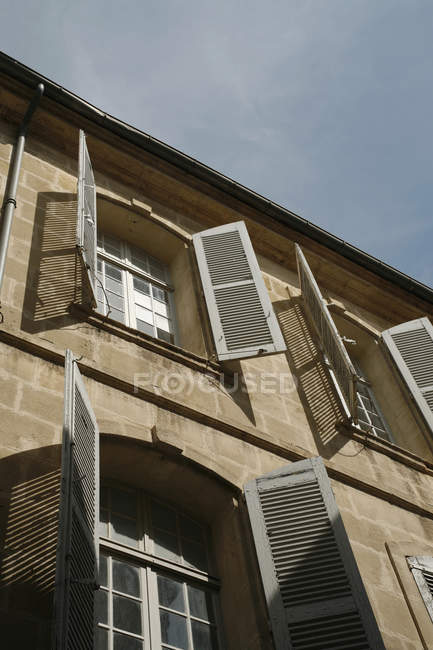 Low angle view of facade with open window shutters — Stock Photo