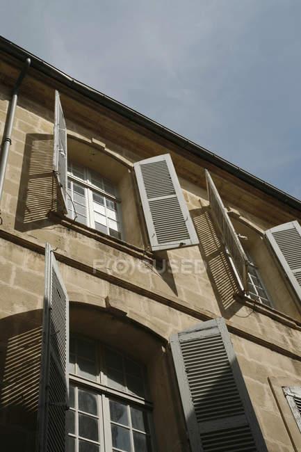 Vista ad angolo basso della facciata con persiane aperte — Foto stock
