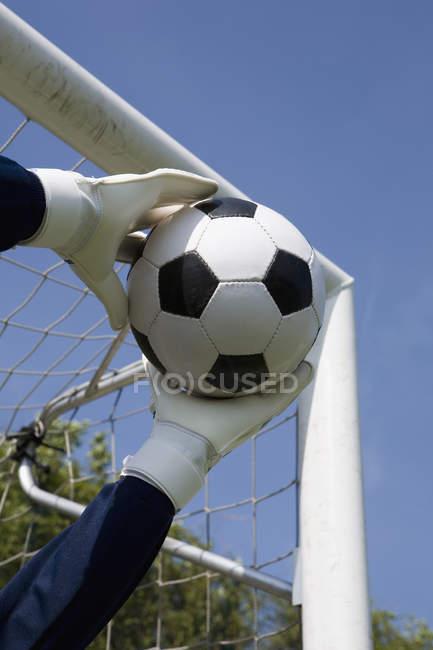 Рукавичках воротаря в руках лову футбольний м'яч у ворота посаду — стокове фото