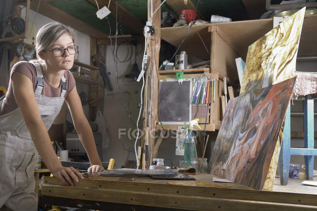 A young woman considering her painting in an art studio — Stock Photo