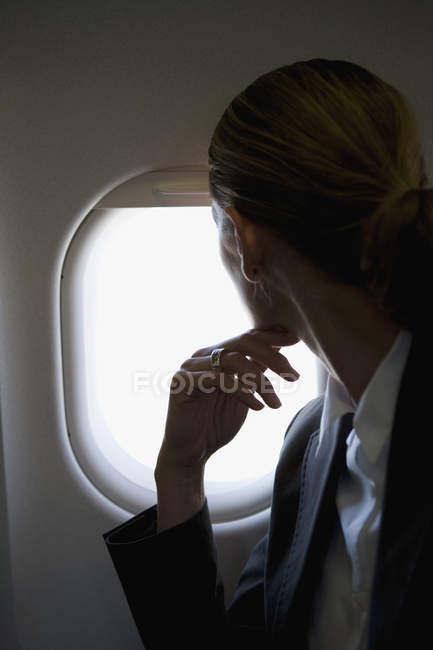 Rear view of female passenger looking through window of plane — Stock Photo