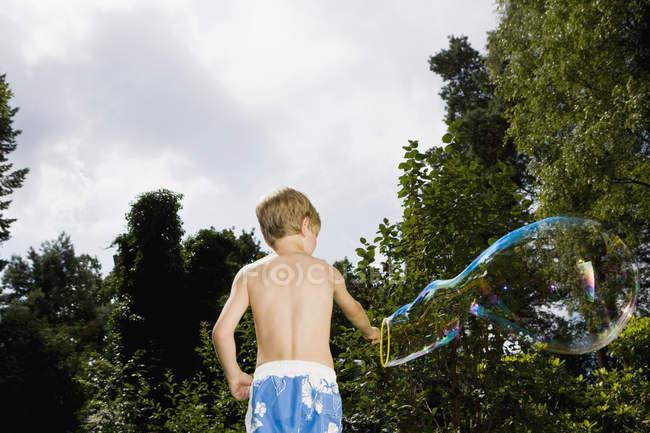 Junge eine Blase mit einem Blase Wand im Garten — Stockfoto