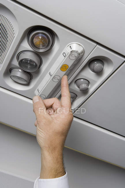 Crop male hand pressing call button on airplane — Stock Photo