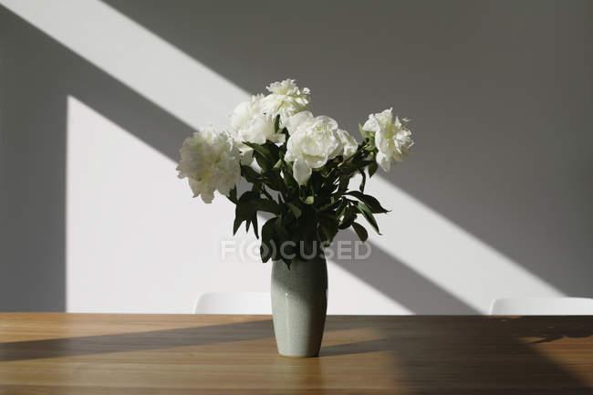Ceramic vase of white peonies wooden table — Stock Photo