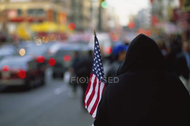 Visão traseira da pessoa encapuzada segurando bandeira americana na rua da cidade — Fotografia de Stock