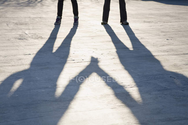 Shadows of two people holding hands on asphalt — Stock Photo
