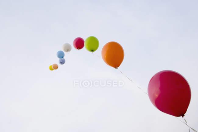 Гелієм повітряних куль прив'язані до рядка ширяють у небі — стокове фото