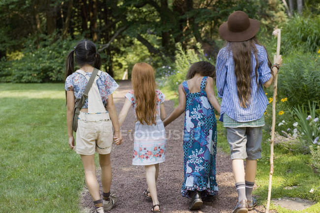 Rear view of four girls walking down path at park — Stock Photo