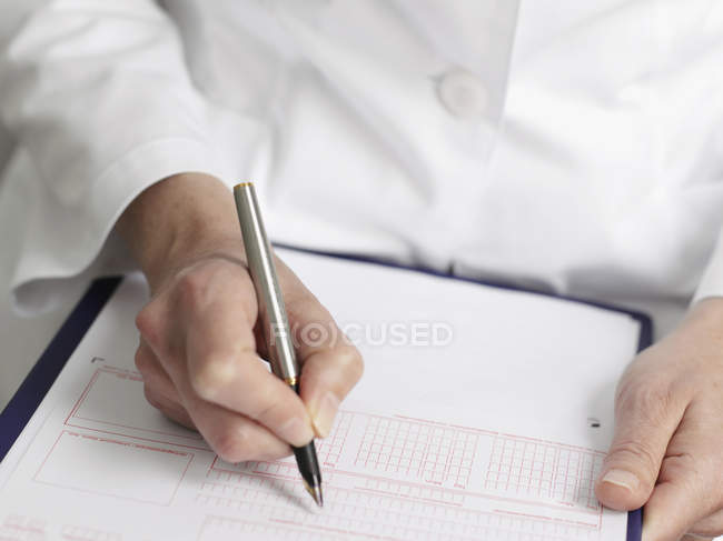 Doctor's hands filling out paper blank — Stock Photo