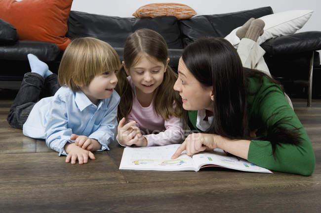 Una madre leyendo un libro a sus dos hijos - foto de stock