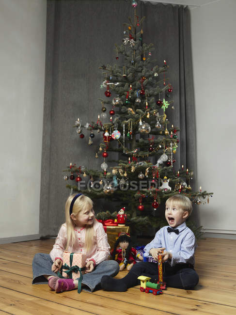 A girl and boy playing with presents in front of a Christmas tree — Stock Photo
