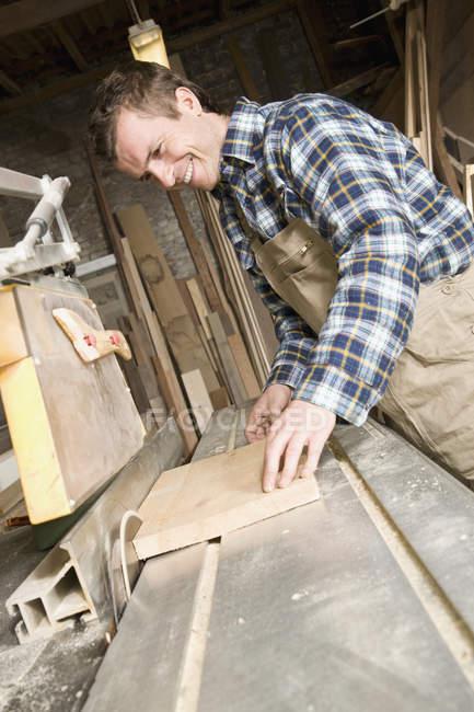 Lächelnder Schreiner sägt Holz in Werkstatt — Stockfoto